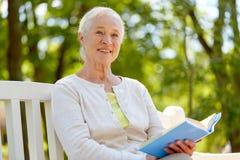 Den lyckliga höga kvinnaläseboken på sommar parkerar royaltyfri fotografi