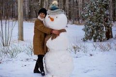 Den lyckliga höga kvinnan hugger och kramar en stor verklig snögubbe Arkivbilder