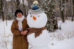 Den lyckliga höga kvinnan hugger och kramar en stor verklig snögubbe Fotografering för Bildbyråer