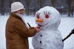 Den lyckliga höga kvinnan hugger och kramar en stor verklig snögubbe i vinter Royaltyfria Bilder