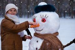 Den lyckliga höga kvinnan hugger och kramar en stor verklig snögubbe i vinter Royaltyfri Fotografi