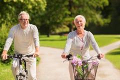 Den lyckliga höga parridningen cyklar på sommar parkerar royaltyfri bild