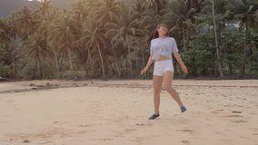 Den lyckliga handelsresandeflickan k?r p? den tomma stranden i den h?rliga rosa solnedg?ngen, hopp och skratt som ?r fulla av lyc lager videofilmer