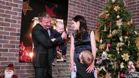 Den lyckliga helgdagsaftonen för ` s för det nya året för familjen, ståenden av en lycklig familj, föräldrar och barn spenderar t stock video