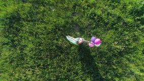 Den lyckliga helgen surrsikt av den tonåriga flickan med kulört hår har gyckel med ballonger på gräsmatta arkivfilmer