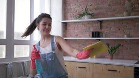 Den lyckliga hemmafrun i grov bomullstvilloveraller och handskar dansar med den rengöringsmedelsprej och dammtrasan i händer un
