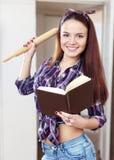 Den lyckliga hemmafrun läser boken för recept Royaltyfri Bild