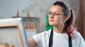 Den lyckliga id?rika unga kvinnliga m?laren fokuserade att arbeta p? konststudiomedeln?rbilden lager videofilmer