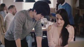 Den lyckliga japanska affärsmannen och européaffärskvinnan talar på arbetstabellen i multietnisk kontorsultrarapidnärbild stock video