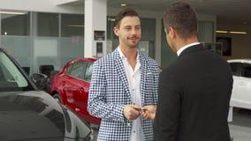 Den lyckliga köparen och säljaren gör ett avtal av att köpa en bil arkivbild