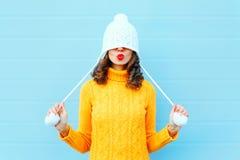 Den lyckliga kalla flickan som blåser röda kanter, gör luft att kyssa att bära en stucken hatt, gul tröja över blått Arkivfoton
