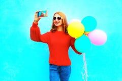 Den lyckliga kalla flickan tar en bild självståenden på en smartphone Royaltyfri Foto