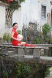 Den lyckliga kinesiska kvinnan i röd cheongsam turnerar på den forntida staden Arkivfoton