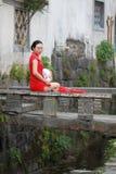 Den lyckliga kinesiska kvinnan i röd cheongsam turnerar på den forntida staden Royaltyfri Foto