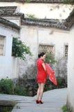 Den lyckliga kinesiska kvinnan i röd cheongsam turnerar på den forntida staden Arkivbild