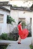 Den lyckliga kinesiska kvinnan i röd cheongsam turnerar på den forntida staden Royaltyfria Bilder