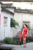 Den lyckliga kinesiska kvinnan i röd cheongsam turnerar på den forntida staden Royaltyfri Bild