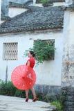 Den lyckliga kinesiska kvinnan i röd cheongsam turnerar på den forntida staden Fotografering för Bildbyråer