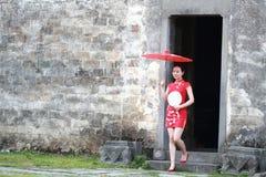 Den lyckliga kinesiska kvinnan i röd cheongsam turnerar på den forntida staden Arkivbilder