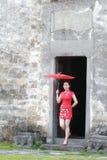 Den lyckliga kinesiska kvinnan i röd cheongsam turnerar på den forntida staden Royaltyfri Fotografi