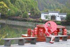 Den lyckliga kinesiska kvinnan i röd cheongsam turnerar på den forntida staden Royaltyfria Foton