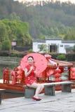 Den lyckliga kinesiska kvinnan i röd cheongsam turnerar på den forntida staden Arkivfoto