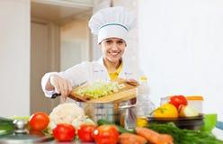 Den lyckliga kocken arbetar med grönsaker Royaltyfria Bilder