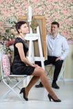 Den lyckliga konstnären målar ståenden av den nätta kvinnan Arkivfoto