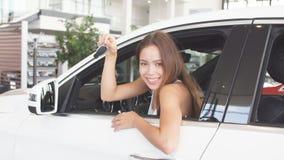 Den lyckliga kvinnachauffören i den vita bilen rymmer biltangenter i hennes nya bil på rum för bilshowen lager videofilmer