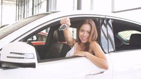 Den lyckliga kvinnachauffören i den vita bilen rymmer biltangenter i hennes nya bil på rum för bilshowen arkivfilmer