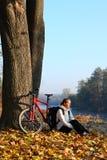 Den lyckliga kvinnacyklisten tycker om rekreationhösten i natur Royaltyfria Bilder