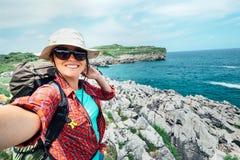 Den lyckliga kvinnafotvandrarehandelsresanden tar ett selfiefoto på fantastisk nolla fotografering för bildbyråer