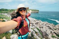 Den lyckliga kvinnafotvandrarehandelsresanden tar ett selfiefoto på fantastisk nolla royaltyfri foto