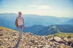 Den lyckliga kvinnahandelsresanden i bergen och landskapet av berg och blå himmel reser livsstilbegrepp av affärsföretaget Royaltyfri Bild