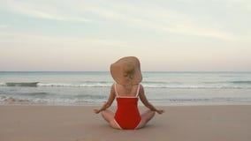 Den lyckliga kvinnahandelsresanden i röd baddräkt och hatten som mediterar i lotusblomma, poserar på en perfekt strand arkivfilmer