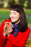 Den lyckliga kvinnainnehavkoppen av varmt te i höstligt parkerar, hösten Royaltyfria Bilder