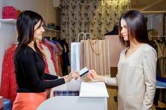 Den lyckliga kvinnakunden som betalar med kreditkorten i mode, shoppar arkivfoton