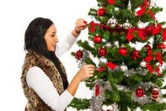 Den lyckliga kvinnan dekorerar julgranen Arkivbild