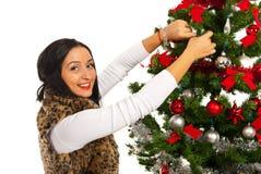 Den lyckliga kvinnan dekorerar julgranen Arkivbilder