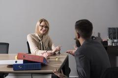 Den lyckliga kvinnan diskuterar företagspengar med mannen Kvinnaframstickandeleende med finansiären i regeringsställning Affärskv arkivbilder