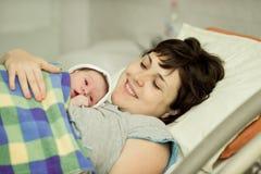 Den lyckliga kvinnan efter födelse med ett nyfött behandla som ett barn Royaltyfri Bild