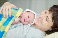 Den lyckliga kvinnan efter födelse med ett nyfött behandla som ett barn Royaltyfria Foton