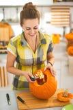 Den lyckliga kvinnan förbereder stor orange pumpa för allhelgonaaftonparti Royaltyfri Bild