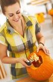 Den lyckliga kvinnan förbereder stor orange pumpa för allhelgonaaftonparti Fotografering för Bildbyråer