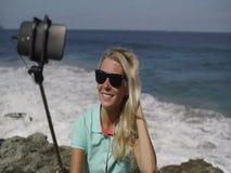 Den lyckliga kvinnan gör selfiefotoet på en smartphone på stranden arkivfilmer