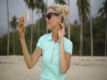 Den lyckliga kvinnan gör selfiefotoet på stranden lager videofilmer