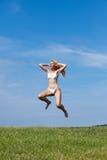 Den lyckliga kvinnan hoppar i ett sommargräsplanfält Arkivfoto