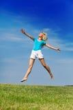 Den lyckliga kvinnan hoppar i ett sommargräsplanfält mot den blåa himlen. Stående i en solig dag Royaltyfri Foto