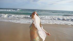 Den lyckliga kvinnan i bikini och skjortan som går på havet, sätter på land och lyftte händer Ung härlig flicka som tycker om liv stock video
