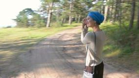 Den lyckliga kvinnan i blå vändande och roterande runda för turban i skog semestrar begrepp stock video